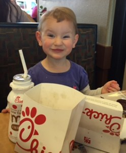A two-year-old girl with a pixie face, squinting with a smile, has a bottle of chocolate milk and Chick-fil-A containers in front of her. She is sitting in a booth, wearing a purple shirt with white sleeves.