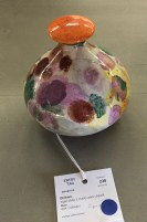 A close up of a shiny polka dot vase of brown, purple, green, yellow and white with a speckled orange top. Taped underneath the vase is a string with a white label identifying vase. The label also has a blue dot sticker on it.