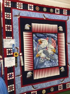 Bald Eagles border and take center stage in this red, white and blue quilt with a star pattern around edge. The center is three ferocious bald eagle heads with two flags flying behind them in a cloudy blue scene.