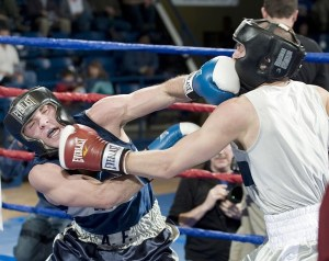 Two boxers in a ring are going at it with boxer on the left jabbing at the chin while boxer on the right delivers a blow on an anguished face.