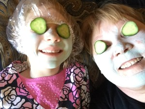A six-year-old and her grandma take a selfie with green facial mask on their faces and sliced cucumbers on their eyes.