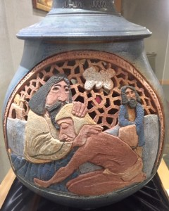A smokey blue pot depicts folk art father and prodigal son embracing with the other son standing in the background.