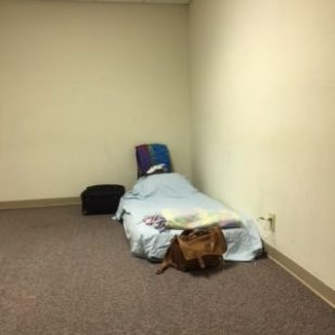 A corner of an empty room, with tan walls and brown carpet, shows an air mattress with sheets and blanket on it and a blue and purple towel draped over a folding chair, with black suitcase and tan travel bag on the side and end of mattress.