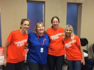 Three smiling middle age women in orange shirt and one smiling woman in blue shirt link arms for photo.