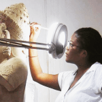 close up of Alexandra McDougle doing restoration work on a Cambodian statue