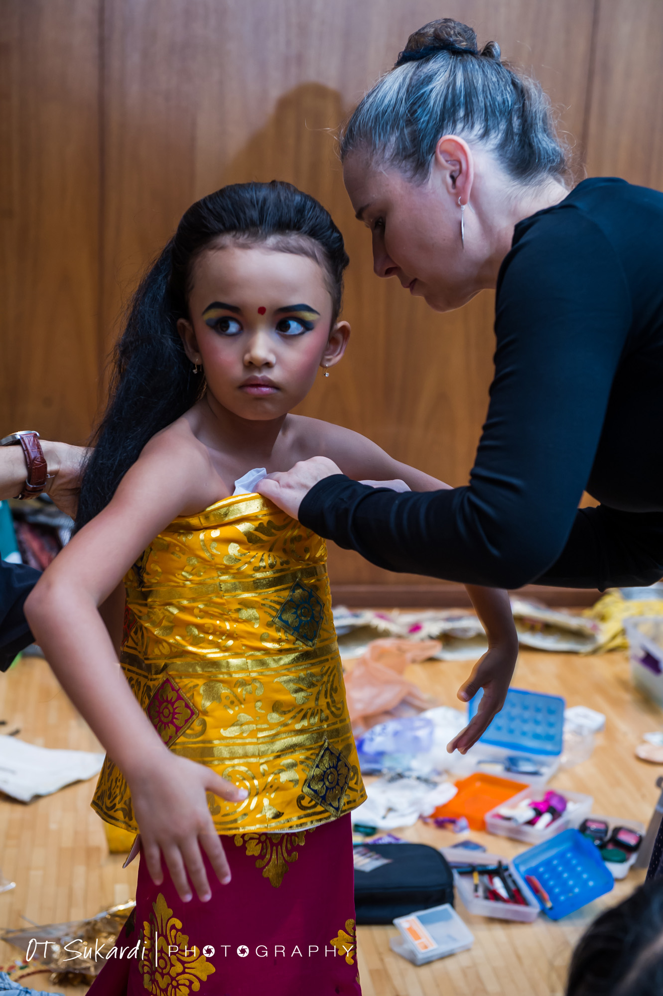 Young performer being wrapped in gold sash