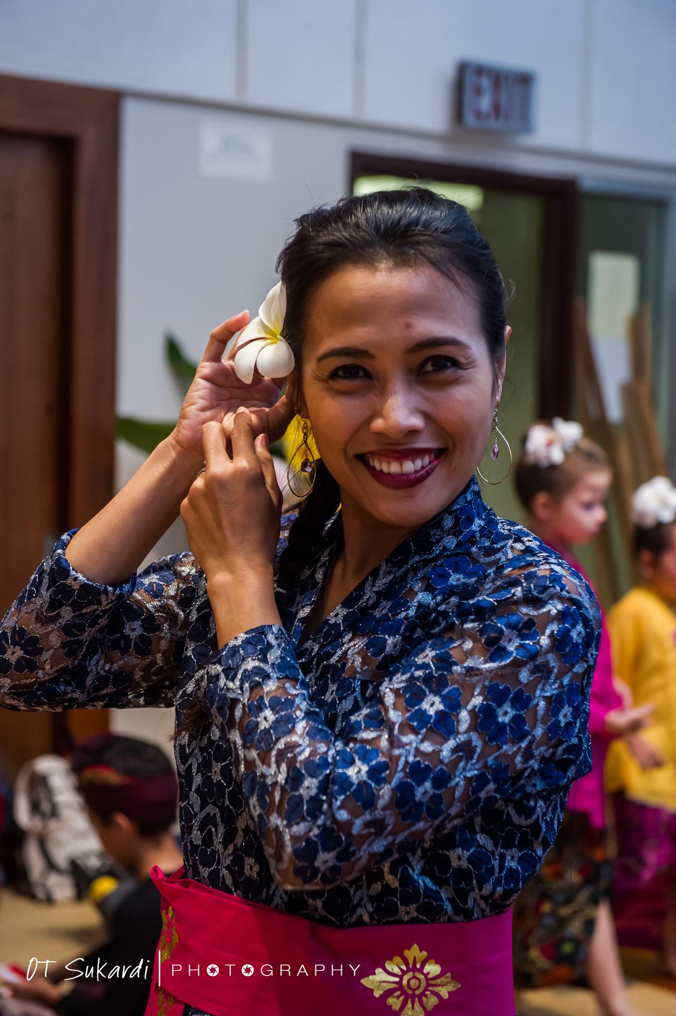 smiling performer fixing flower in her hair