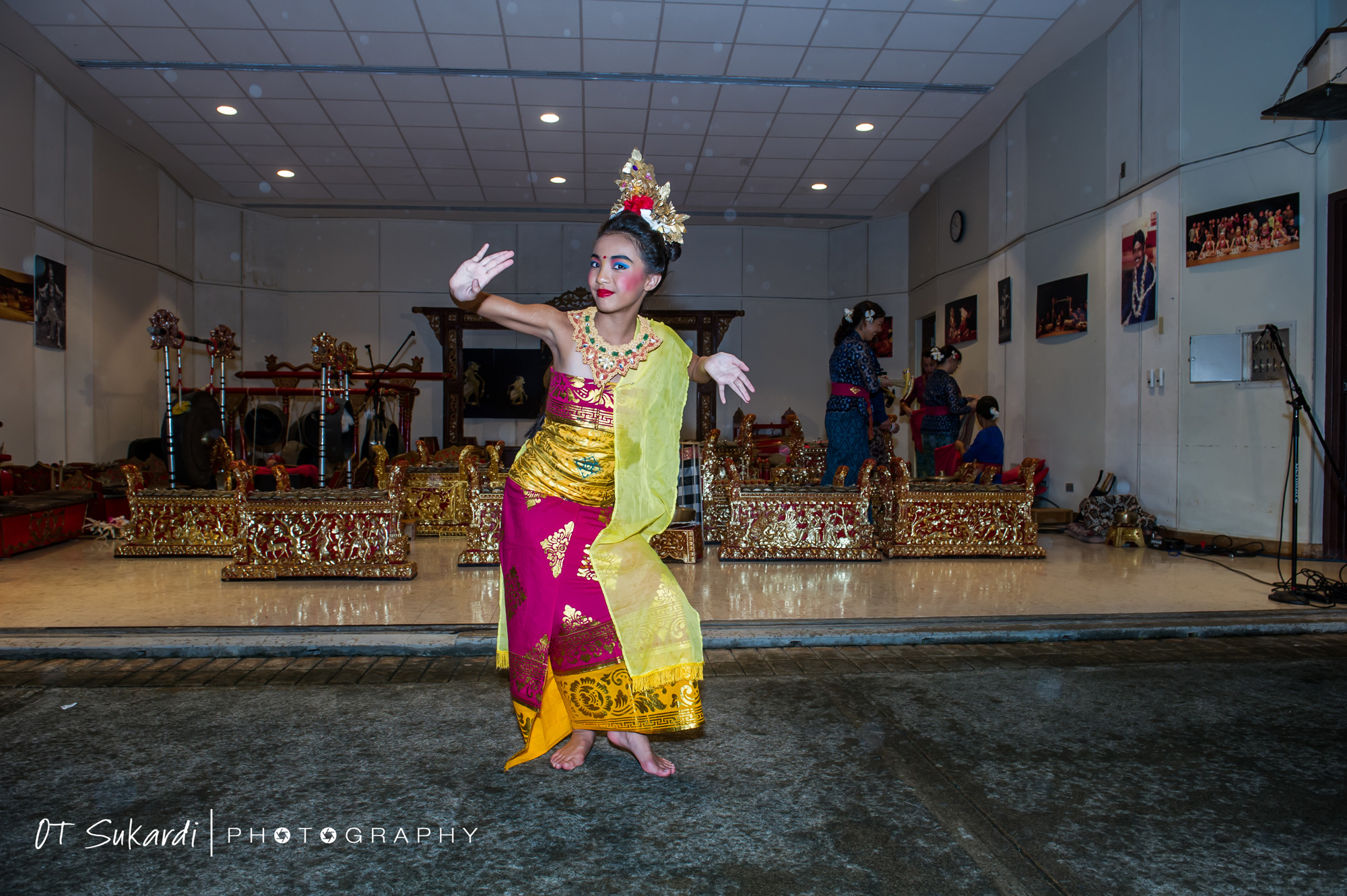 girl performer poses in ornate pink and yellow costume
