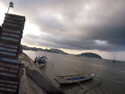 Transporting a karaoke machine on a small fishing vessel as a storm arrives in Quezon