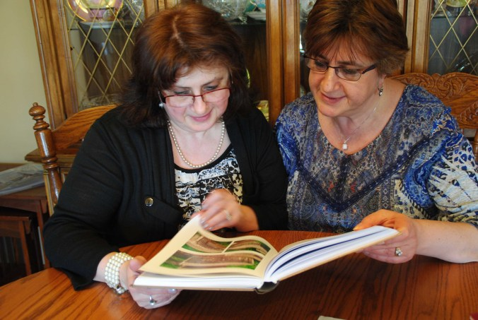 Pirumova sisters looking over a recently-published Russian book about their family history - photo by C.S. Hagen