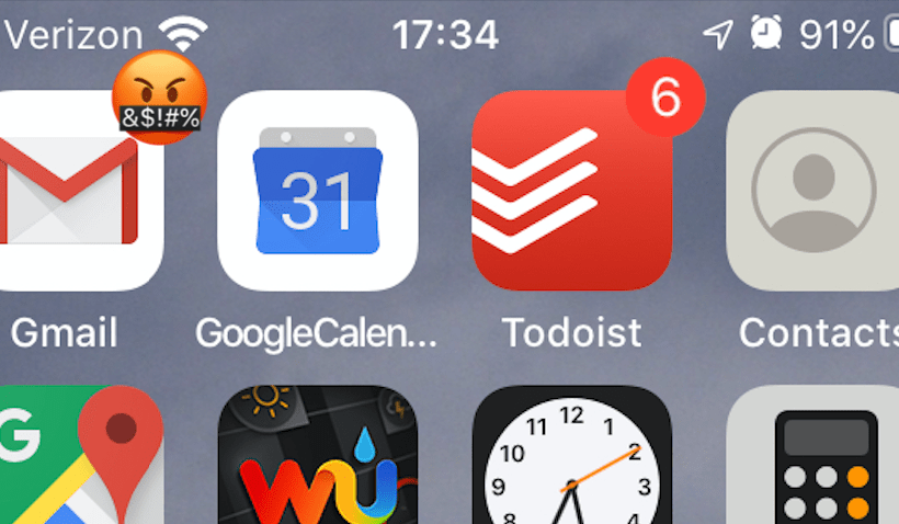 An iPhone home screen with an angry face on the e-mail app icon
