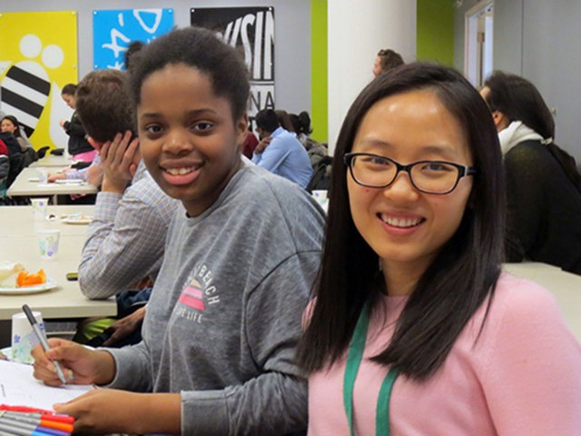 African-American student and adult mentor at a technology company cafeteria, both smiling