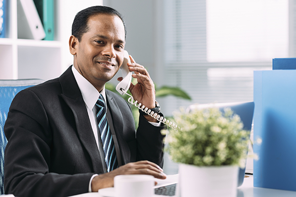 Indian manager talking on the telephone at his workplace