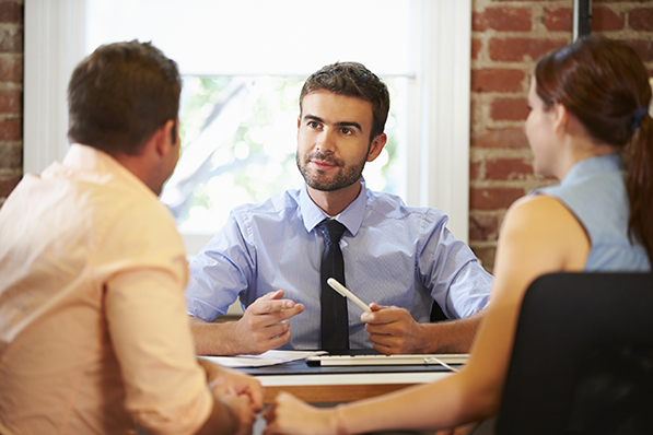 Couple Meeting With Financial Advisor In Office