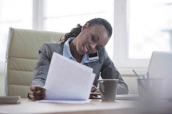 Portrait of businesswoman working with laptop writes on a document and calling phone at her office