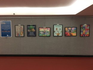 6 colorful posters, finalists in the Fair Housing poster contest, hanging on a wall in the Legislative Office Building