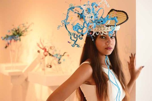 Julissa Ragunauth wears a hat created by artist Daniel Lanzilotta. Behind her are some of Lanzilotta's sculptures.