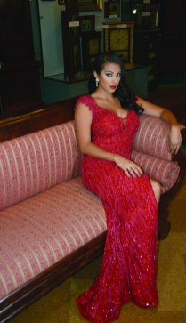 Alyssa Taglia poses inside the American Clock and Watch Museum in Bristol in a red gown.