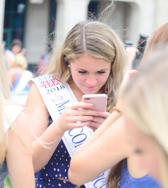 Miss Connecticut's Outstanding Teen Morgan Mancini reviews a photograph taken of her sister queens.