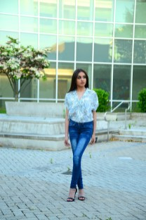 Model Iraima Lopez wears a New Day resort short sleeve button down down in white floral from Target (Target.com). Jeans are the model's own.