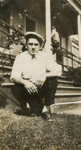 Orville W Garrison squatting by porch stairs cigarette in hand