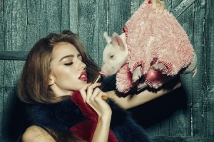 Woman putting lipstick on pig