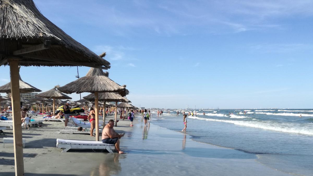 valuri sezlonguri plaja turisti