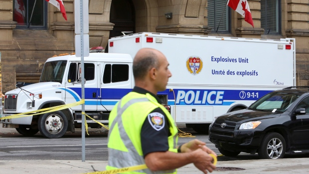 A police officer cordons off an area using tape outside the Langevin building across from the Parliament buildings in Ottawa, Wednesday, Oct. 16, 2013. (Fred Chartan / THE CANADIAN PRESS)