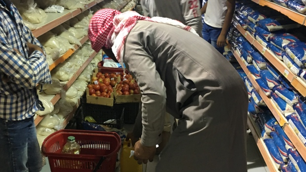 A man carefully selects his groceries.