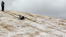 A man slides down a hill after a rare snowfall in Johannesburg, South Africa, on Tuesday, Aug. 7, 2012. (AP Photo/Themba Hadebe)