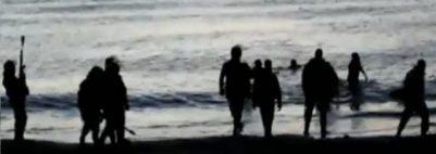 Captura del vídeo donde se ve a unos inmigrantes cruzando a nado la frontera y a unos agentes, en tierra.
