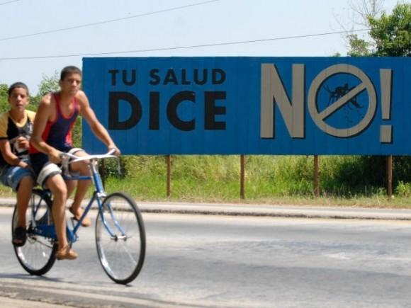 Cubanos en bicicleta pasan por delante a una propaganda de la campaña para erradicar el mosquito que transmite el dengue hemorrágico.