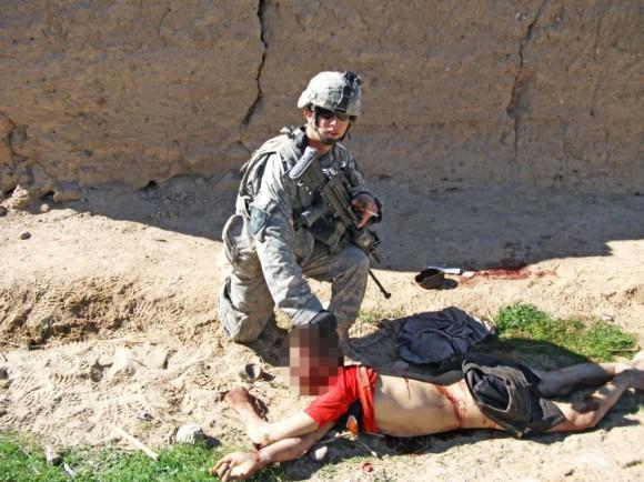 """Esta imagen muestra el cuerpo de Gul Mudin, el hijo de un agricultor, quien fue asesinado el 15 de enero de 2010. Un miembro del """"equipo de matar"""" está posando detrás de él. Der Spiegel publicó sólo tres fotos de los cerca de 4.000 imágenes y vídeos que ha visto. Los procedimientos judiciales marciales contra los soldados involucrados en los asesinatos son para comenzar en breve."""