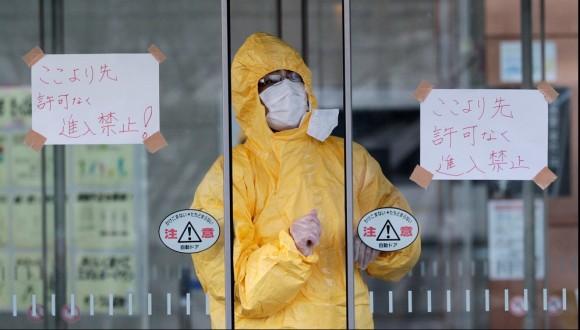 """Un técnico mira a través de una puerta automática donde se puede leer """"No entrar salvo, personal autorizado"""". Foto: Reuters"""