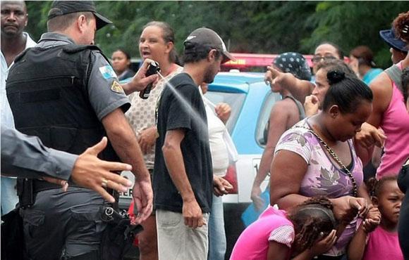 Marzo de 2011. Un policía de Río de Janeiro, Brasil, rocía con spray de pimienta a una niña que acompaña a su madre en una manifestación por las ayudas sociales en la conocida ciudad brasileña. El agente fue expedientado y condenado