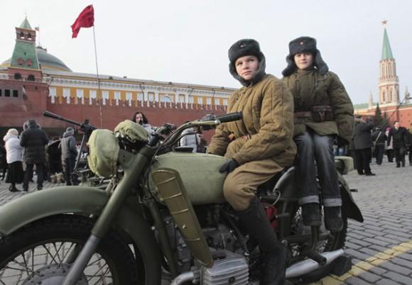 Un par de niños rusos vestidos con uniformes de la II Guerra Mundial sentados en una vieja motocicleta durante un desfile militar celebrado en la Plaza Roja de Moscú (Rusia) hoy, lunes 7 de noviembre de 2011. El desfile conmemora el 70º aniversario del histórico desfile de 1941 cuando el ejército soviético cruzó por la plaza mientras se dirigía al frente durante la II Guerra Mundial. EFE/Sergei Ilnitsky
