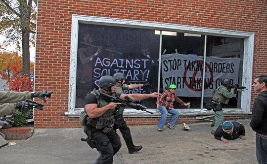 """Un equipo SWAT de más de 25 policías fuertemente armados invadieron un grupo de arrestados Ocupar y spin-off de los anarquistas en Chapel Hill NC que se había hecho cargo de un concesionario de coches por mucho tiempo abandonado y el espacio se utilizará sugerido para una clínica gratuita, cocina, cuidado de niños, biblioteca, dormitorios y otros usos mucho menos miedo que el equipo SWAT que nos quedamos sin palabras. Se dijo que la policía sintieron que tenían que tomar la acción semi-automática-manejo Debido a que """"el grupo utilizó grandes pancartas para ocultar las ventanas de los negocios ..."""" Lo siento. Todavía estamos sin palabras."""