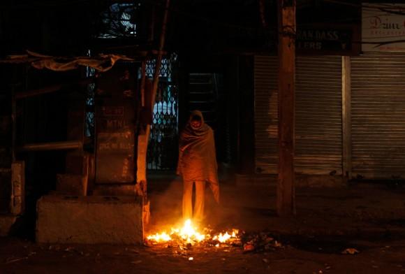 Un hombre sin hogar se mantiene caliente cerca de una fogata en el pavimento en Nueva Delhi, India, 13 de diciembre. (Foto: Mustafa Quraishi / Associated Press)