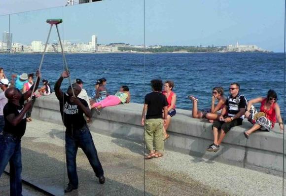 Limpieza del espejo momentos antes de la inauguración de la obra Realidad (Happily Ever After) de Rachel Valdés Camejo, con motivo de la Oncena Bienal de La Habana 2012, en el malecón habanero, Cuba. Foto:Tony Hernández Mena/AIN