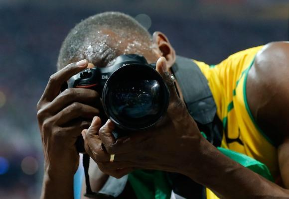 Bolt juega con una cámara tras ganar la final de los 200 metros