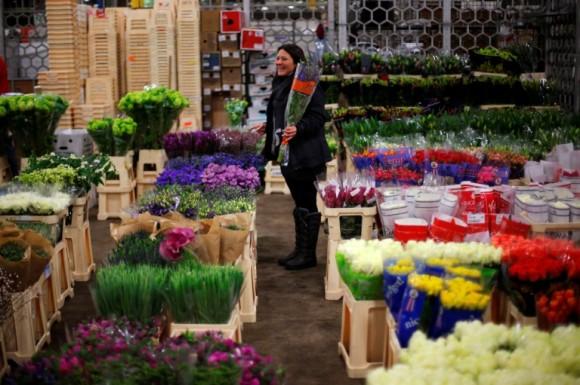 Un vendedor sonríe mientras sostiene un ramo de flores en el mercado de New Covent Garden en la víspera del día de los enamorados en Londres. Foto: Andrew Winning / Reuters