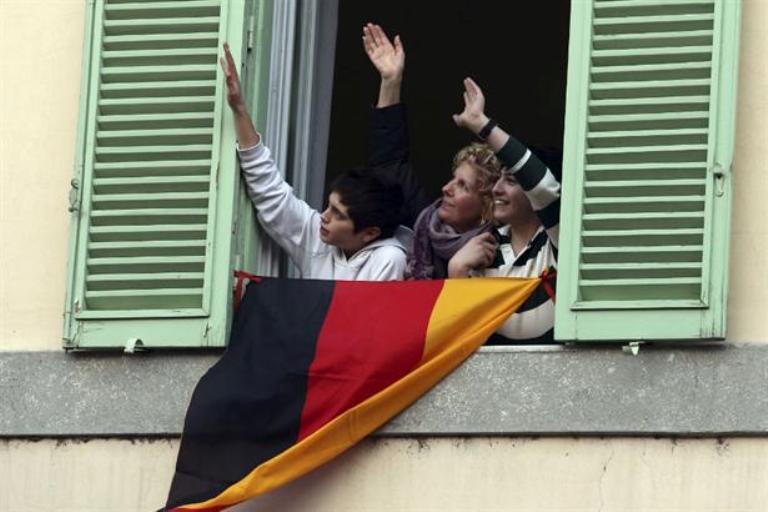 Unos fieles logran acaparar la atención del alemán Ratzinger con una bandera de su país frente a la ventana de Castelgandolfo. Foto AP