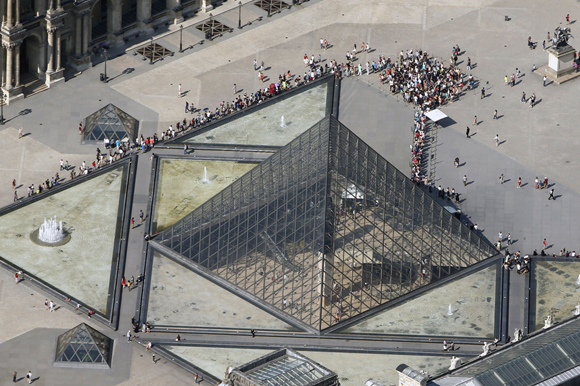 An aerial view shows people waiting outside the Pyramid of the Louvre Museum in central Paris