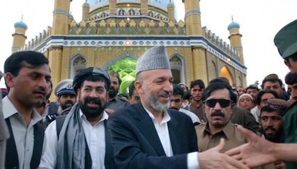 Tomas van Houtryve / ASSOCIATED PRESS - Haji Gulalai, entonces un jefe de inteligencia afgano, está en las gafas de sol a la derecha del presidente afgano Hamid Karzai en 2002 Gul Agha Sherzai, gobernador de Kandahar, se encuentra al otro lado de Karzai..
