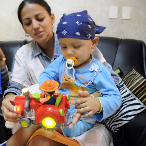 Paciente de la sala de pediatría del  Instituto Nacional de Oncología y Radiología (INOR), recibe un juguete donado por la Cooperativa de Créditos y Servicios  Fortalecida (CCSF), Frank País García del municipio de Alquízar, de la provincia de Artemisa, en La Habana, Cuba el 15 de agosto de 2014.  AIN FOTO/Abel PADRÓN PADILLA