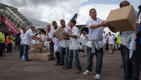 Los primeros miembros de un equipo de 165 médicos cubanos y trabajadores de la salud descargan cajas de medicamentos y material médico de un avión a su llegada al aeropuerto de Freetown para ayudar a la lucha contra el Ébola en Sierra Leona, el 2 de octubre de 2014 FLORIAN PLAUCHEURFLORIAN PLAUCHEUR / AFP / Getty Images