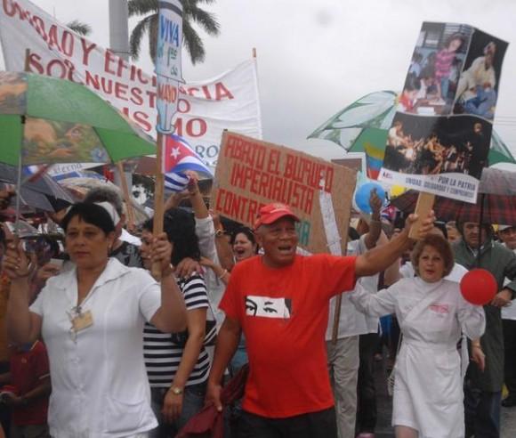 Espirituanos desfilan bajo la lluvia en saludo al Primero de Mayo, Día Internacional de los Trabajadores, en la PLaza Mayor General Serafín Sánchez Valdivia, en Sancti Spíritus, Cuba, el 1ro. de mayo de 2015. AIN FOTO/Oscar ALFONSO SOSA