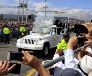 Pope Francis waves to faithful as he arrives to celebrate mass at the Bicentenario Park in Quito