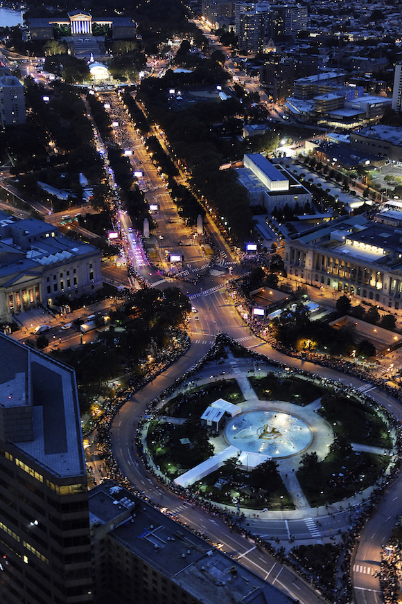 Benjamin Franklin Parkway in Philadelphia is lit up at dusk and lined with tens of thousands of people as Pope Francis makes his way along the thoroughfare, Saturday, Sept. 26, 2015. The pontiff attended a music-and-prayer festival there Saturday night to close out the World Meeting of Families, a Vatican-sponsored conference of more than 18,000 people from around the world. (AP Photo/Michael Perez)
