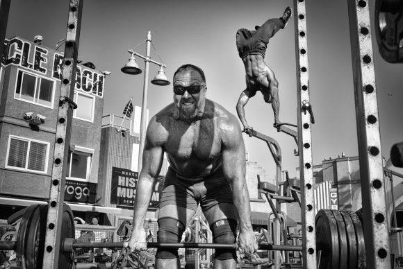 """Un levantador de pesas alza una pesada barra cargada con platos mientras un fisicoculturista se para de cabeza en el aire en Muscle Beach Gym en Venice Beach, California"". Dotan Saguy / National Geographic Travel Photographer of the Year Contest"
